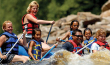 Group of adults and kids whitewater rafting on Lehigh Gorge River.