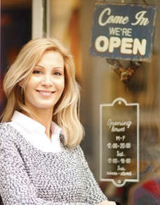 Female business owner in front of her store.