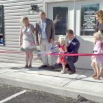 Family cutting ribbon at Load and Lock Self Storage Grand Opening.