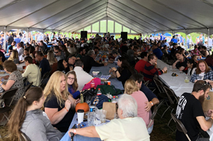 Festival goers enjoying a meal under tent at Oktoberfest.