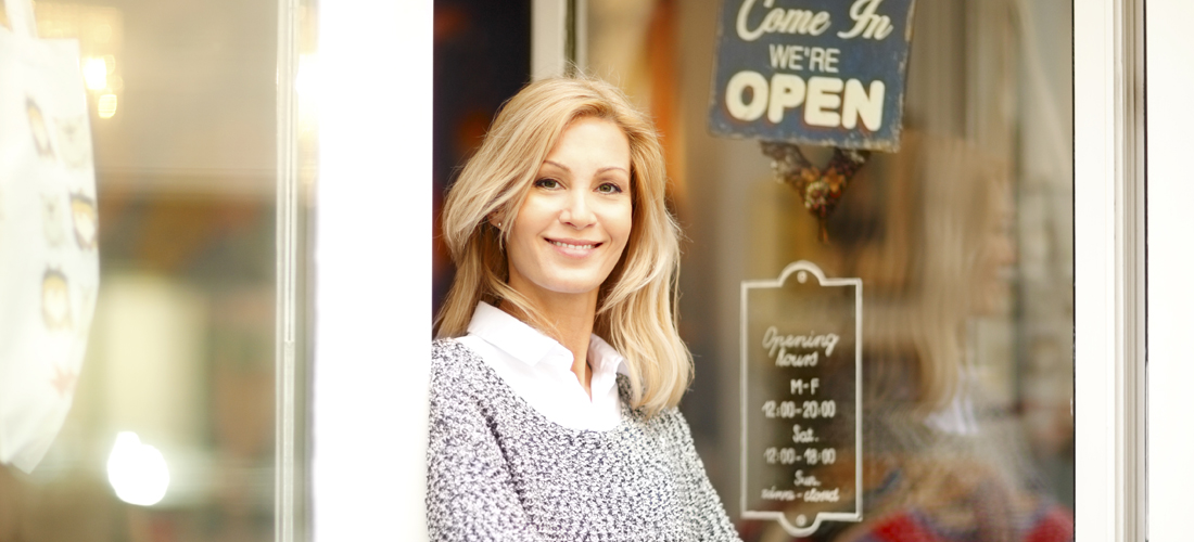 Female business owner in front of her open store.