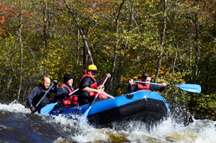 Group of people whitewater rafting down the river during fall foliage in Carbon County.