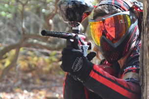 Male skirmish paintball player near a tree.