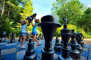 2 children playing with lifesize chess peices