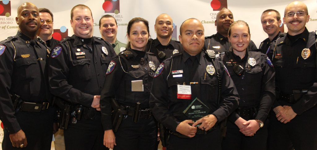 group of police officers smiling at camera in uniform