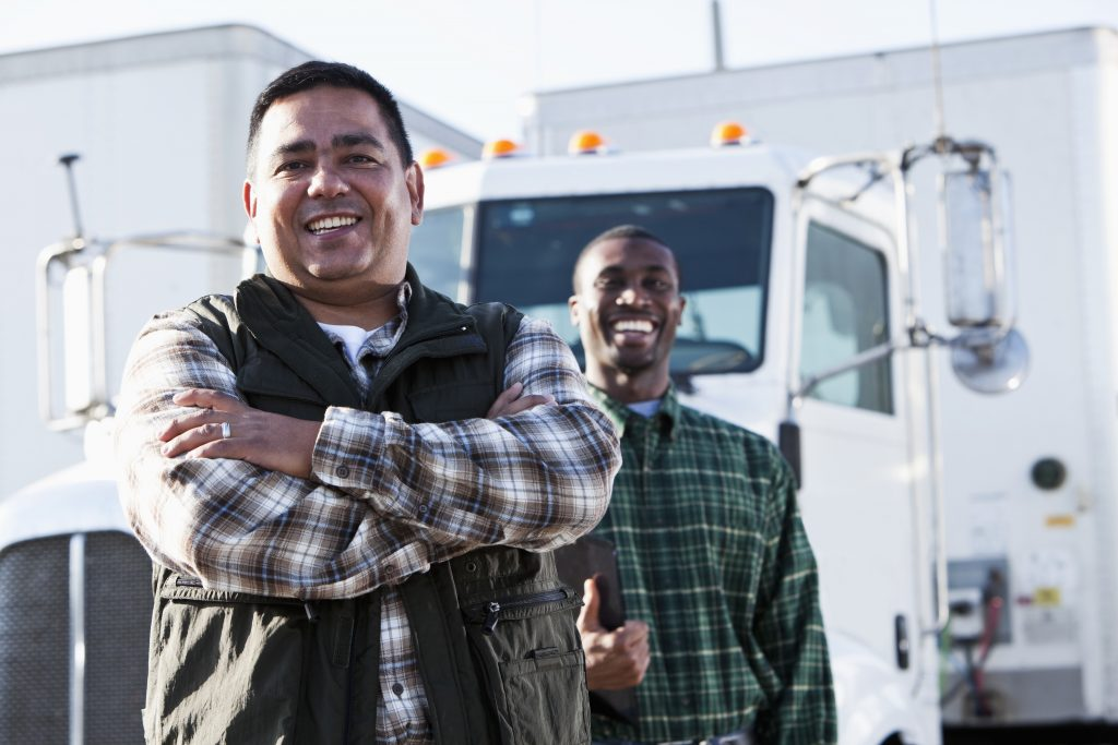 Hispanic and African American truck drivers standing in front of semi-truck.  Focus on Hispanic man (40s).