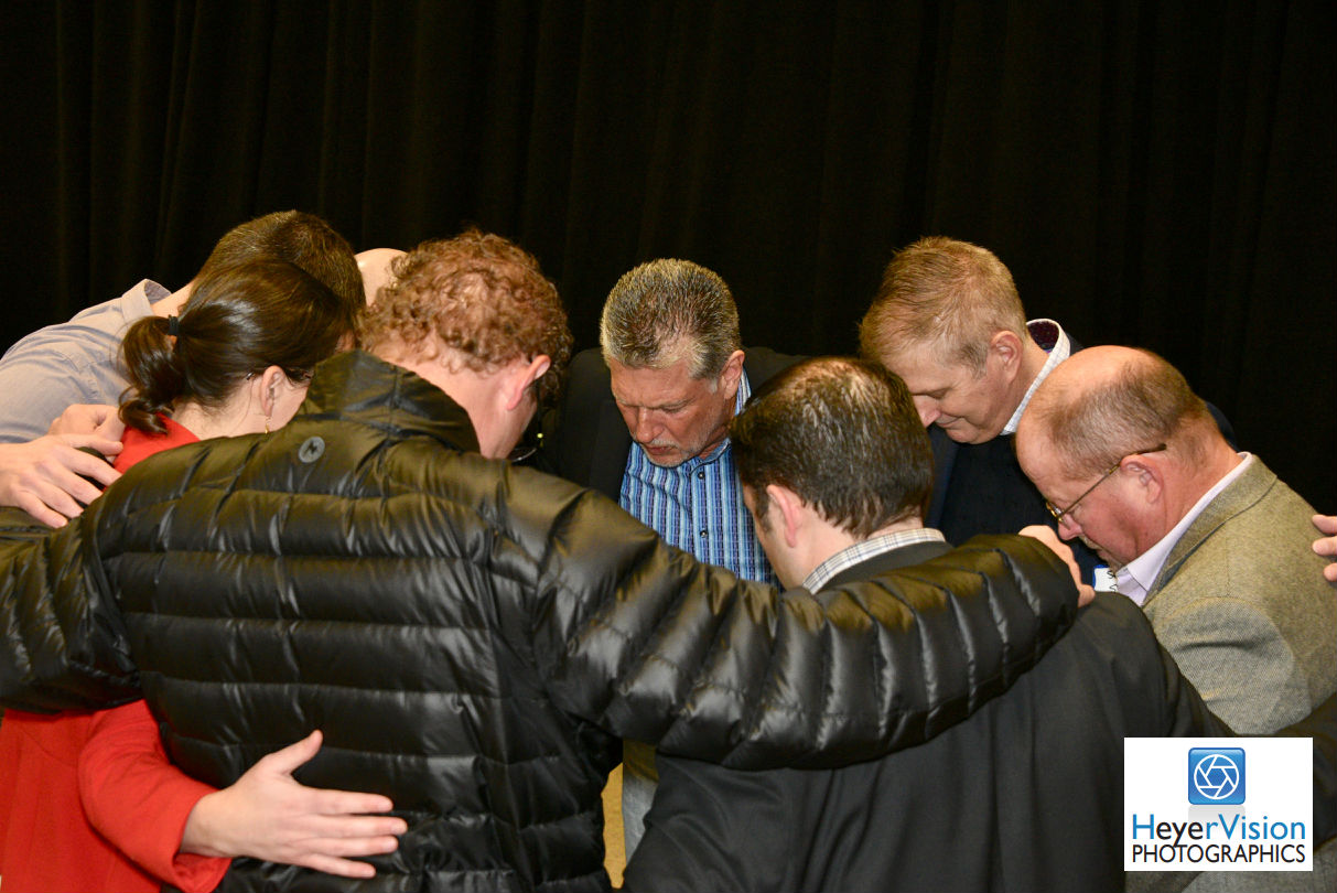 A group of organizers pray before an event - prayer is important to businesses of all membership levels.