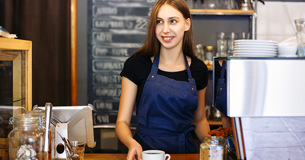 Portrait of a cute young woman at a bar counter. A barista girl in an apron serves a ready espresso in a cafe. Coffee business concept. Small local business.