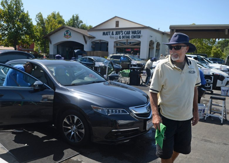 Matt Broderick, co-owner of Matt and Jeff's Car Wash, walks among client cars as his staff cleans them in Novato Wednesday. (Alan Dep/Marin Independent Journal)