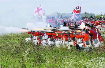 The Bristish troops fire during the 225th aniversary reenactment of the Battle of Saratoga Saturday afternoon on a farm in Ft. Edward. Saturday's battle was the Freeman's farm battle, and on Sunday the Bemis Heights battle will be fought.  (photo by Tom Killips)  10/12/2002