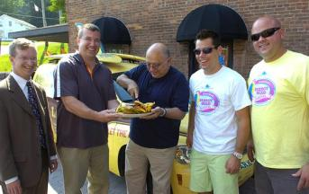 Town of Milton Supervisor Dan Lewza helps steady the plate as Ballston Spa Mayor John Romano cuts the ceremonial cheeseburger Wednesday to promote this weekend's Parrot Head Festival at the Saratoga County Fairgrounds and its accompanying Jimmy Buffet-themed events in the village of Ballston Spa. Saratoga County Chamber of Commerce President Todd Shimkus and festival promoters Garth Ellms and A.J. Bodden looked on at The Factory in Ballston Spa. (ED BURKE/eburke@saratogian.com)