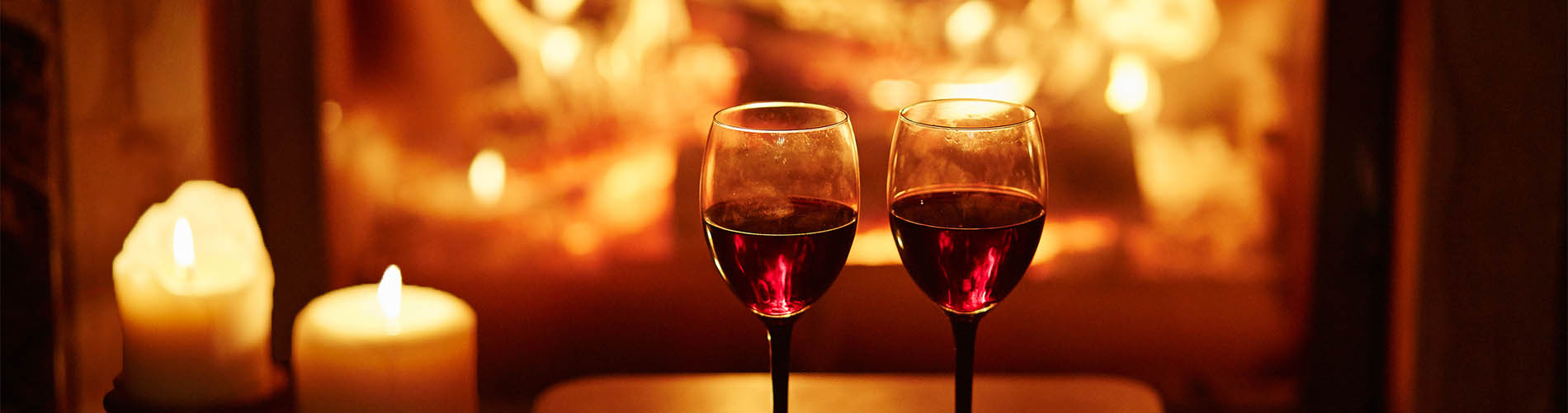 Two glasses of red wine near fireplace with many candles.