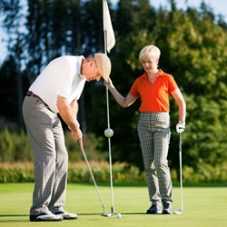 Man putting on golf green woman holding flag