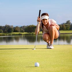 woman golfer lining up putt