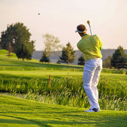 male golfer hitting ball over water on golf course