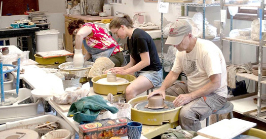 pottery making class with students working on wheels