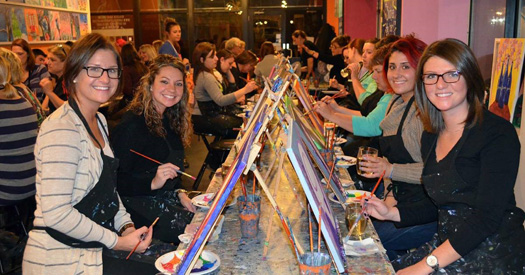 group of people painting on table easels