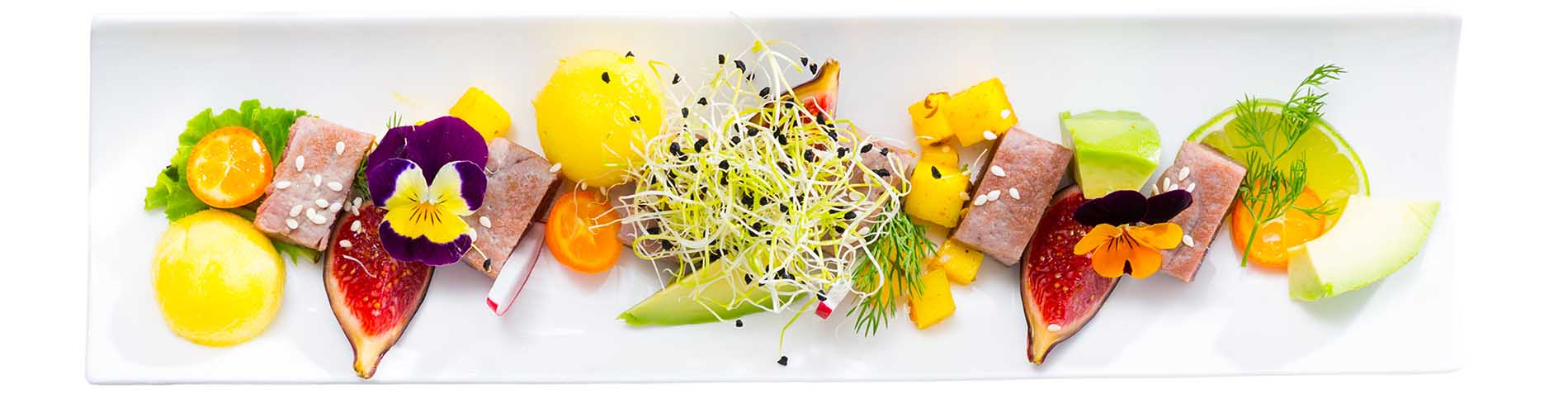 Close up of tasty fried tuna with mango and avocado, served with fig and flower. Isolated over white background
