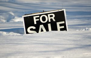 Real estate for sale sign partially buried under a very heavy snowfall