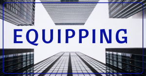 Image of buildings in black and white with the word equipping over them.