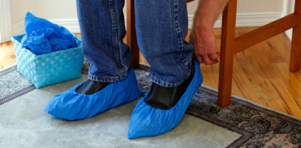 Putting on shoe covers to help keep a customer's home more clean