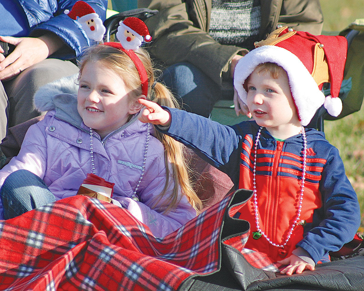 "Grace Golembiewski, 6, left, and Garrett Weyand,5, both from Shelby Township, watch the passing spectacle curbside.  Celebrating the town bicentennial with a ""vintage Christmas"" theme, the 66th Annual Rochester Hometown Christmas Parade rolled down Main Street boasting a carnival of dancers, marching bands, floats, and Santa Claus in Rochester, Michigan on December 3, 2017.   (Photo by Brandy Baker)"