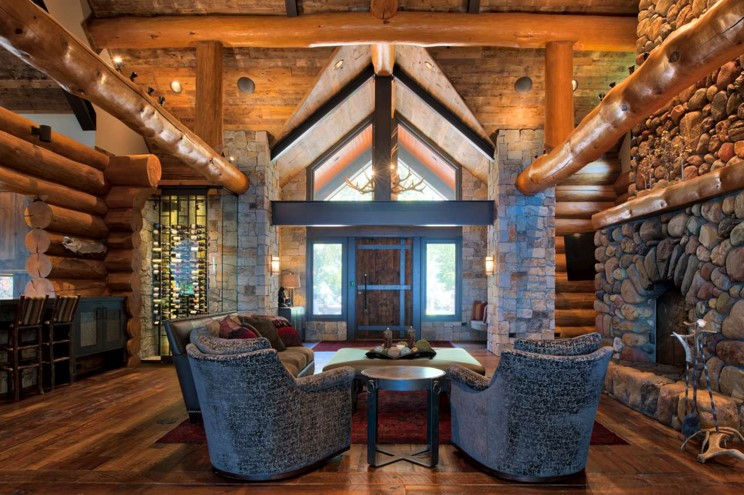Entryway and living room remodel featuring logs and stone pillars with stone fireplace